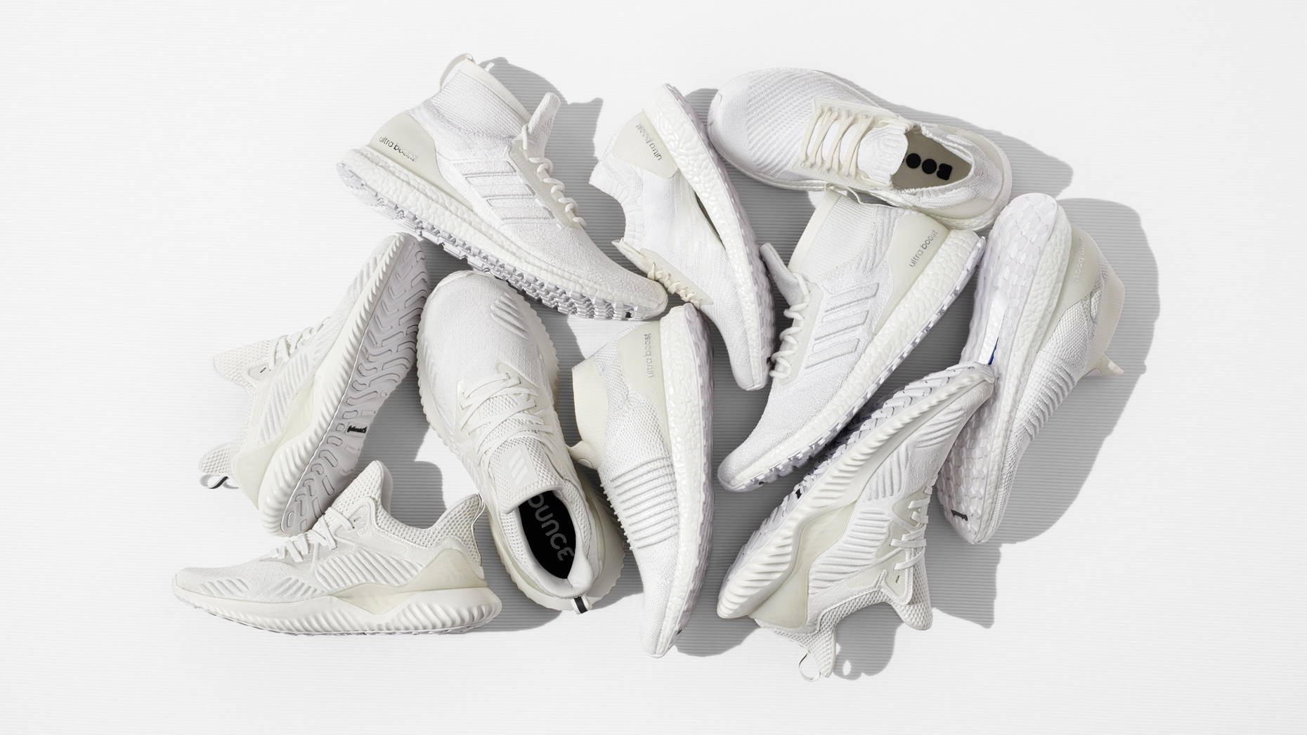 Adidas white Ultraboost shoe collection arranged on white surface overhead view